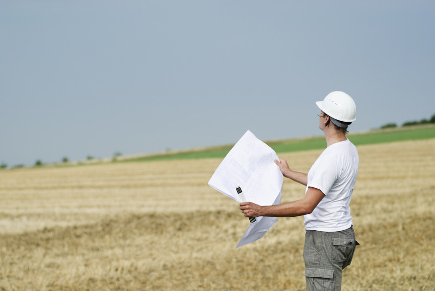 a construction worker looking at land