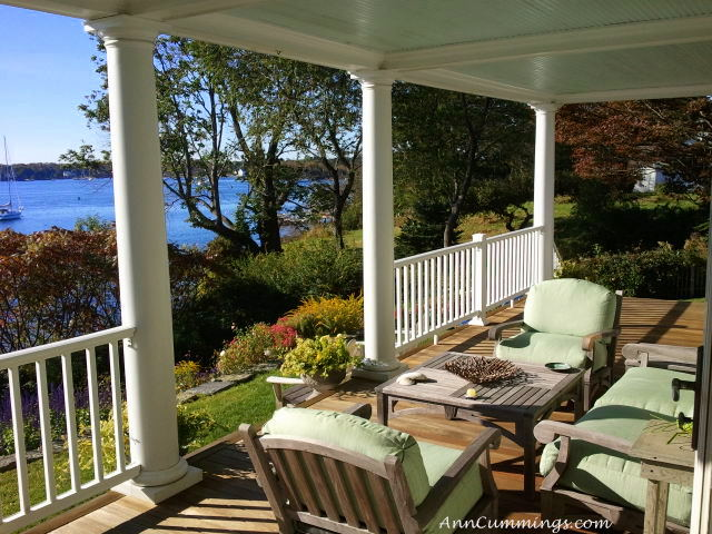 Three outdoor patio chairs on a large front porch overlooking a bay.